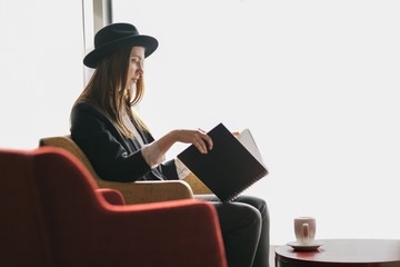 Young woman sitting on the couch reading