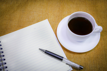 coffee in white cup with notebook for memory.
