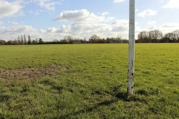 A Close Up Of A Goal Post On A Field In The Sun With Blue Sky And Clouds