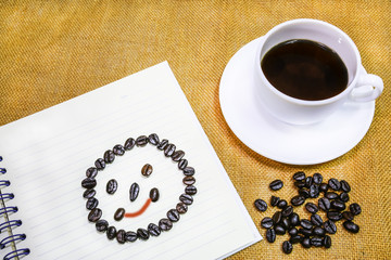 coffee in white cup with smile round face on notebook.