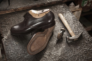 Pair of leather shoes, awl and hammer in a cobbler's shop