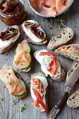 Foto op Plexiglas Voorgerecht Appetizers. Toasts with salmon, dried tomatoes and sweet peppers