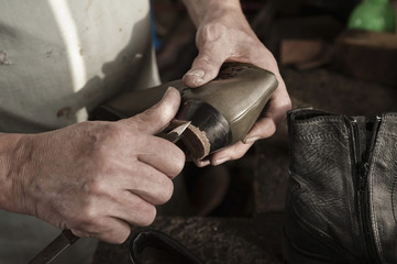 Close up of shoemaker working in workshop
