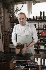 Portrait of shoemaker holding pair of leather shoes