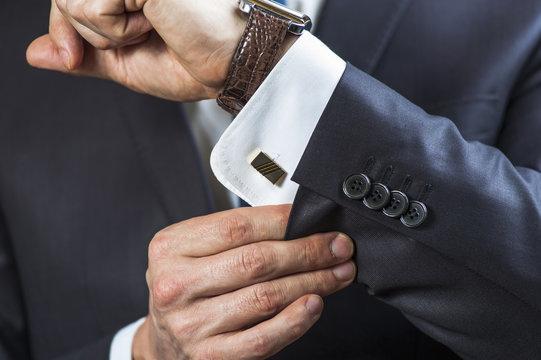 Elegant man correcting his cufflinks and sleeve.