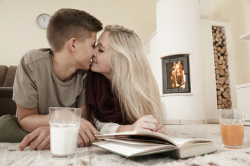 Teenage couple in love cuddling on carpet in front of fireside