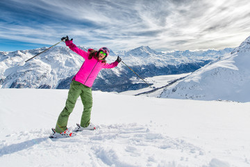 Young girl on skies in winter mountain resort