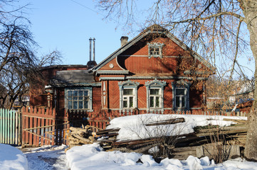 Old wooden house with pile of wood in winter