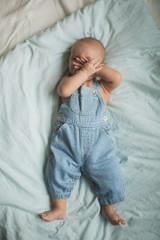 happy baby lying on blue sheet