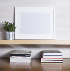 A white picture frame sitting on a wooden shelf with plant and books.