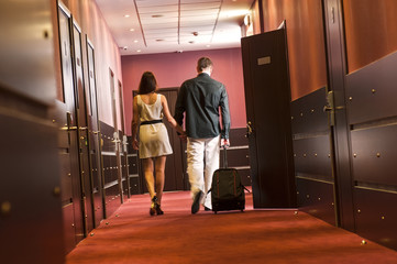 A man and a woman walk down the hall of the hotel with a suitcase.