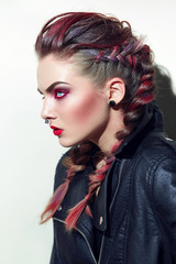 Girl with piercings on her face. Makeup with a rock style. Volume hair, plaited braids. Profile of a girl on a white background in studio. Leather jacket. Painted in red hair.