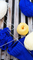 White yellow blue yarn for knitting with spokes are wooden surface