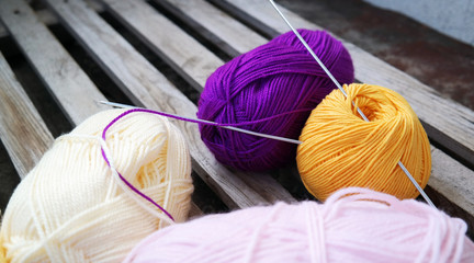 White yellow Purple yarn for knitting with spokes are wooden surface