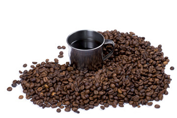 the steel cup of coffee surrounded with coffee grains