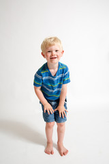Young blonde boy looking at the camera with his hands on his knees.