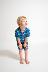 Young blonde boy looking up to his left with his hands on his knees.