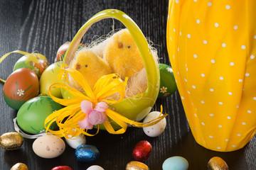 Cestino in ceramica a forma di uovo con nido e pulcini  su un tavolo con ovetti colorati di cioccolato e zucchero