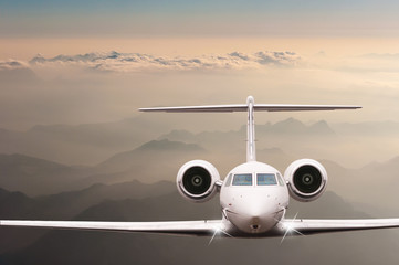 Travel concept. Airplane fly over clouds and Alps mountain on sunset. Front view of a big passenger or cargo aircraft, business jet, airline. Empty space for text