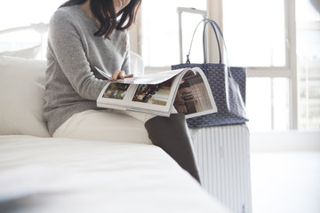 Women are reading a magazine sitting on the bed