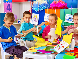 Group kids make applique of colored paper on table in kindergarten .