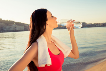 Close up portrait of sportswoman with towel drinking fresh water