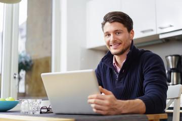 lächelnder mann arbeitet zuhause in der küche am laptop