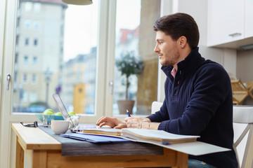 mann arbeitet zuhause mit laptop und unterlagen