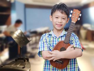 Asian boy with ukulele at music school