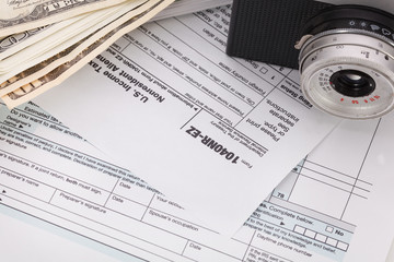 Money and camera on tax form background