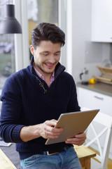 mann sitzt auf dem küchentisch und schaut auf sein tablet