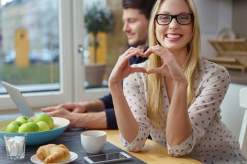 lachende frau sitzt mit ihrem freund in der küche und zeigt ein herz mit den händen