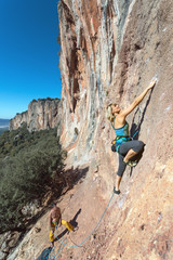Female extreme Climber stepping up on high vertical Rock