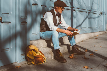 Reading elderly man sitting on the street