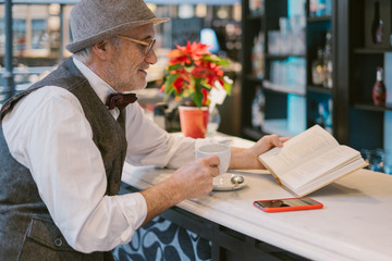 Senior man reading a book in a bar