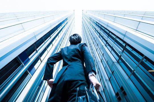 高層ビルを見上げるビジネスマン,ローアングル,オフィスビル