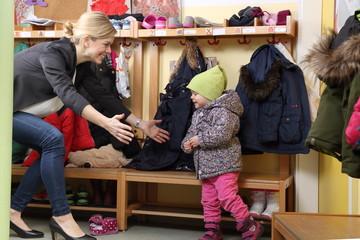 Mutter holt freudig ihr Kind von Kinderkirppe ab
