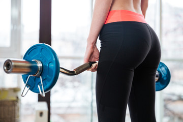 Attractive young sportswoman training with barbell in gym