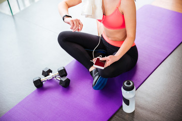 Sportswoman using fitness tracker and smartphone on mat in gym