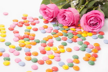 Pink roses on white with color candies