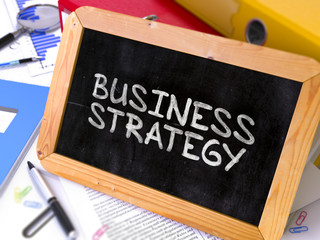 Business Strategy Handwritten by White Chalk on a Blackboard.