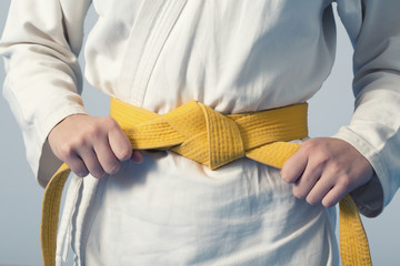 Papiers peints Combat Hands tightening yellow belt on a teenage dressed in kimono for martial arts