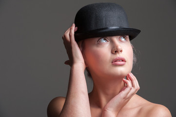 young lady posing in a black bowler hat