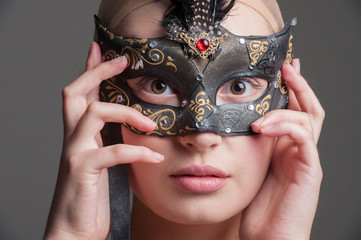 young lady holding a colorful eye mask at her face