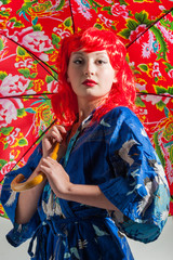 young lady with red hair and colorful umbrella