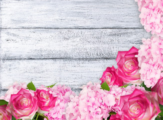 Pink roses and hydrangeas on background of shabby wooden planks