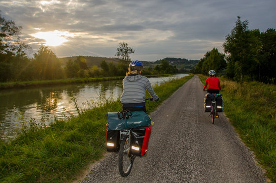 Burgundy, France - CIRCA August, 2015 - Two bikers with panniers cycling near Canal de Bourgogne