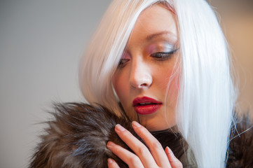 White haired lady wearing a fur coat with colorful make up
