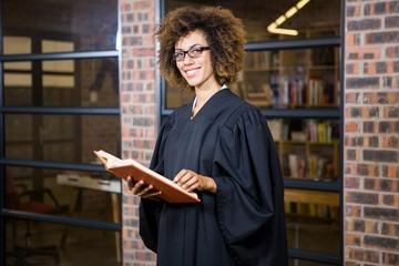 Lawyer standing near library with law book