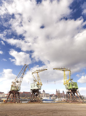 Three old cranes standing by the Odra River in Szczecin, city landmarks in distance.
